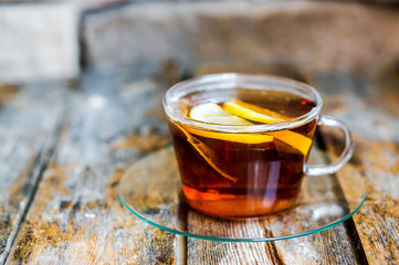 A cup of tea with lemon on rustic wooden background