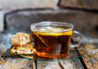 Tea cup with lemon and cookies on rustic wooden background