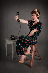 Pinup Girl in Flowered Outfit Excited with Phone Information