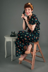 Pinup Girl in Flowered Outfit Grins While on the Telephone