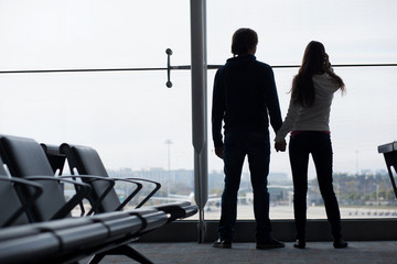 Silhouette of a couple holding hands and waiting at airport