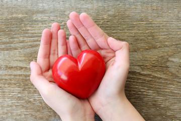 Kinderhände halten ein Herz