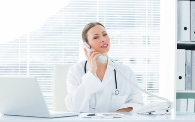 Confident doctor using telephone at desk