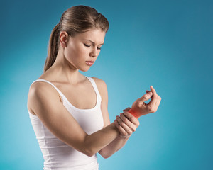 Young woman holding her painful wrist over blue background