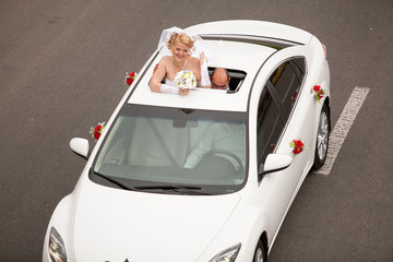 Beautiful blonde bride popping out of car sunroof