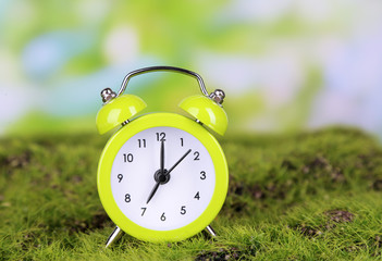 Green alarm clock on grass on natural background