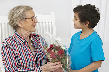 Little boy giving flowers to his grand mother  grandmother's day