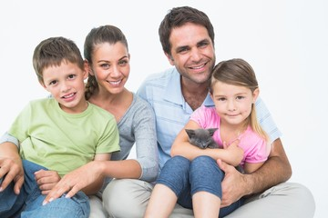 Cute family with pet kitten posing and smiling at camera