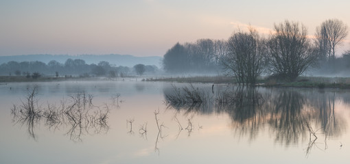 Landscape of lake in mist with sun glow at sunrise - 62523389