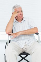 Sad senior man sitting in wheelchair