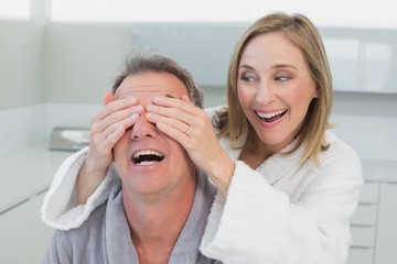Close-up of a happy woman covering man's eyes