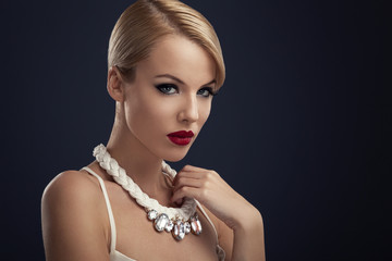 Beautiful blonde with red lipstick and the necklace around the n