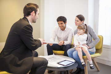 Young Family meeting real-estate agent to buy property