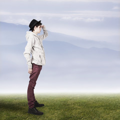 teenager on grass landscape with mountains at the horizon