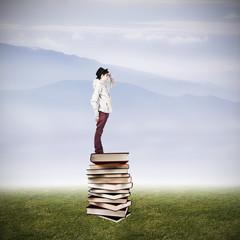 Teen books stacked up watching the horizon