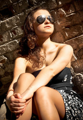 woman in sunglasses sitting against brick wall