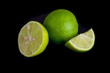 Citrus lime fruit half on black background, small green lemons