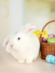 White cute rabbit and Easter eggs in basket