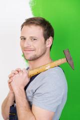 mann mit hammer beim umbau der wohnung