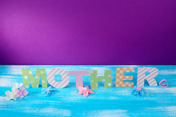 Mother- lettering of handmade paper letters on purple