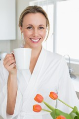 Smiling woman in bathrobe standing with coffee cup