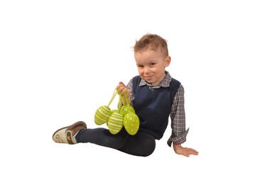 kleiner junge sitzt und hält ostereier