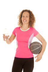 woman orange sports shirt medicine ball and water