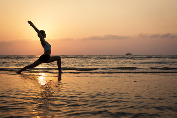 Wall Mural - Yoga silhouette on the beach, virabhadrasana pose