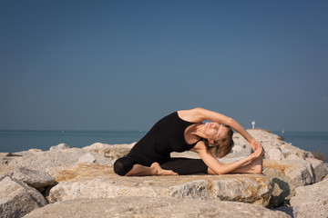 Beautiful woman practicing yoga on the beach