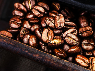Roasted coffee beans macro in a wooden box in vintage manual cof