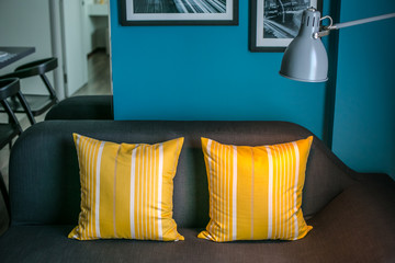 Brown sofa with yellow pillows and lamp