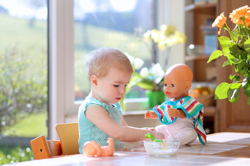 toddler girl feeding with yogurt her dolls sitting in kitchen