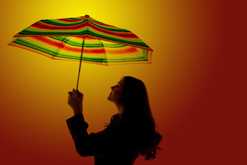 Silhouette of a woman holing a colorful umbrella with an orange