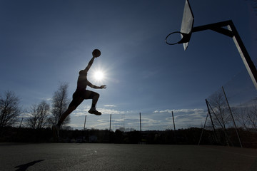 Basketball player silhouette taking off to slam dunk
