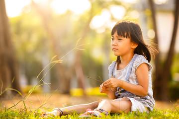 Little asian girl on grass in garden