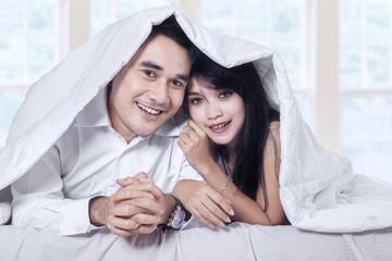 Attractive couple under blanket