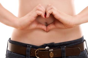 Mädchen zeigt ein Herz vor ihren Bauch