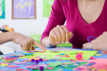 Teacher playing colourful puzzles with kids