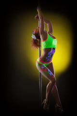 Passionate young go-go dancer posing with pylon