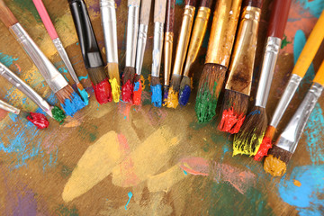 Many brushes in paints on multicolor wooden background
