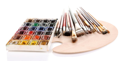 Many brushes on wooden palette, isolated on white