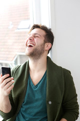 Man laughing with mobile phone