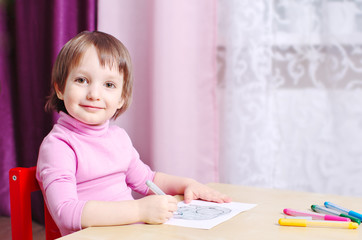 smiling child draws a picture by colorful markers in the room