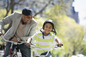 A Family In The Park On A Sunny Day. Father And Son Bicycling