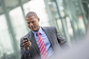 A Young Man In A Business Suit With A Blue Shirt And Red Tie. On A New York City Street. Using A Smart Phone.