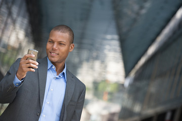 A Businessman In A Suit, With His Shirt Collar Unbuttoned. On A New York City Street. Using A Smart Phone.
