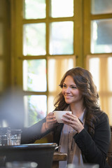 Business People. A Woman In A Grey Jacket Holding A Coffee Cup, Seated At A Table.