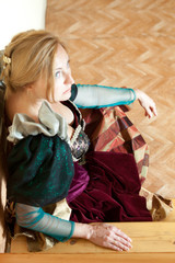 girl in an ancient medieval dress posing against backdrop