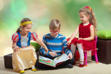 Preteen boy reading a fairy tale to two little girls
