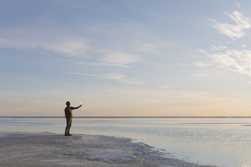 A Man Standing At Edge Of The Flooded Bonneville Salt Flats At Dusk, Taking A Photograph With A Tablet Device.